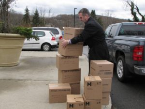 Volunteer Kevin Prendergast stacks cases of stuffing, courtesy of Lisa Pachnos from Project Self-Sufficiency