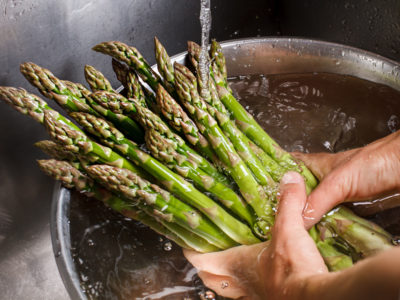 Man's hands washing asparagus. Asparagus under flow of water.