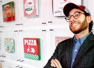 Scott Wiener with wall of pizza boxes