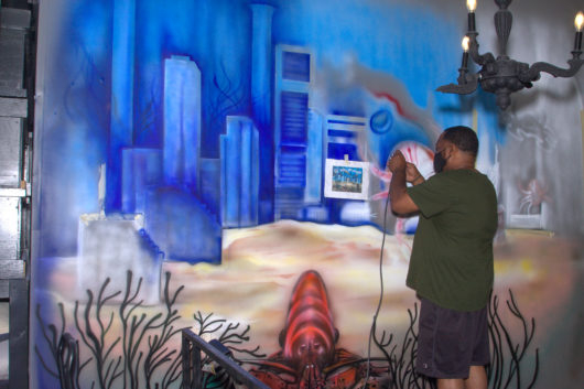 Local artist Marcus Gould painting a mural at Shell n Tail