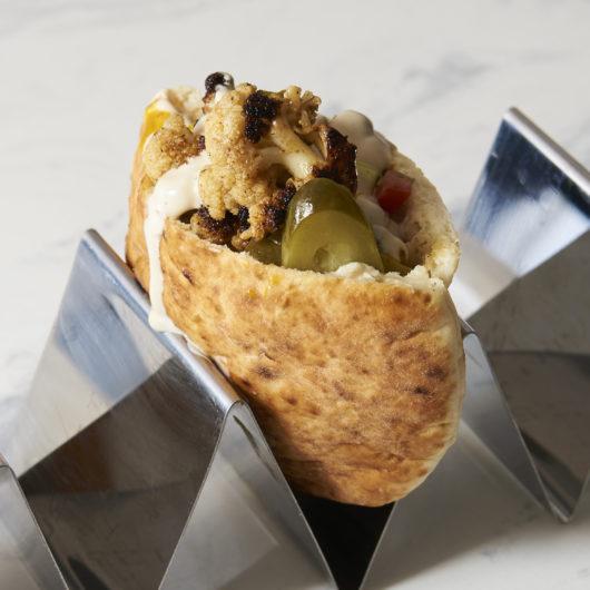 "Shawarma spiced Cauliflower ""al ha plancha"" - w/hummus, tahina, Israeli salad, Amba and sliced pickles"