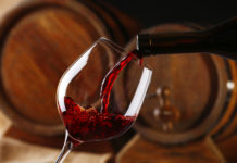 Red wine poured into a glass in front of wine barrels