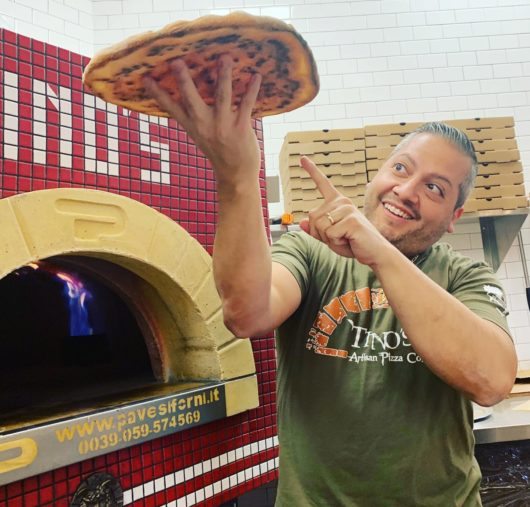 Tino in front of the pizza oven