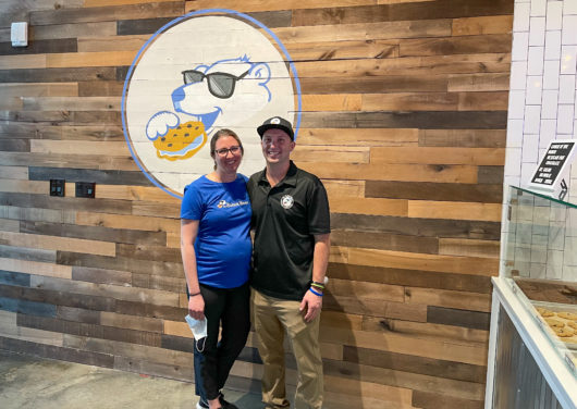 The Baked Bear owners in front of logo