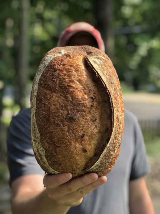 Man holding loaf of bread