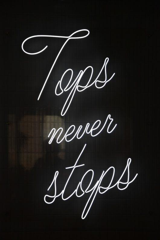 """Tops Never Stops"" neon sign"